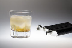 Glass of whiskey and a flask for drinking. Crystal glass with whiskey on ice beside an opened empty black flask laying on its side. It looks cold and refreshing royalty free stock image