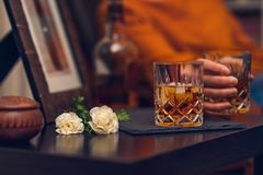 Glass of whiskey and flowers, still life, cinematic effect royalty free stock image