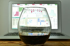 A glass of whiskey in front of a laptop with a stock Ticker on t Stock Photo