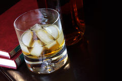 Glass of whiskey and a good book Royalty Free Stock Photo