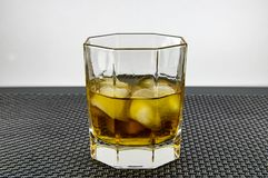 A glass of whiskey and ice. stock photo