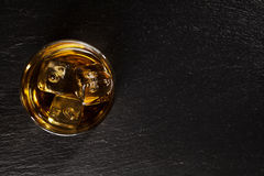 Glass of whiskey with ice on black stone Royalty Free Stock Images