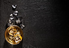 Glass of whiskey with ice on black stone table. Top view with copy space Stock Images