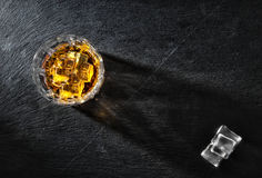 Glass of whiskey with ice on black textural background Royalty Free Stock Photo