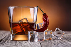 Glass of whiskey with ice and chili. Royalty Free Stock Image
