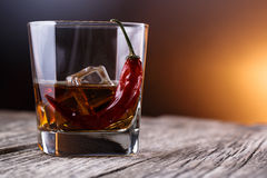 Glass of whiskey with ice and chili. Royalty Free Stock Photography