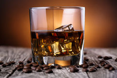 Glass of whiskey with ice and coffee beans. Stock Photography