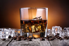 Glass of whiskey with ice and coffee beans. Royalty Free Stock Image