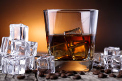 Glass of whiskey with ice and coffee beans. Royalty Free Stock Photo