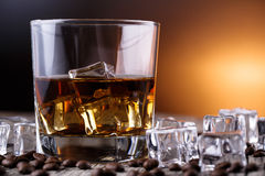 Glass of whiskey with ice and coffee beans. Royalty Free Stock Photos