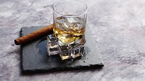 Glass of whiskey with ice cubes and cigar stock video