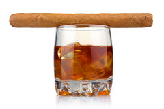 Glass of whiskey with ice cubes and cigar isolated. Glass of whiskey with ice cubes and havana cigar isolated on white background Stock Photo