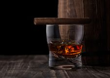 Glass of whiskey with ice cubes and cigar next to wooden barrel. Glass of whiskey with ice cubes and cigar next wooden barrel. Cognac and brandy drink royalty free stock image