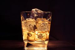 Glass of whiskey with ice cubes on dark background and wood tabl Stock Photos