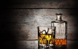 Glass of whiskey with ice cubes and faceted bottle Royalty Free Stock Images
