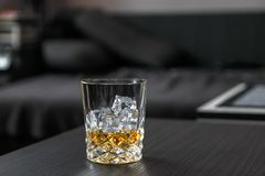 Glass of whiskey with ice cubes stock photography