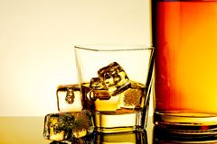 Glass of whiskey with ice cubes near bottle and ice cubes on table with reflection, warm tint atmosphere Stock Photography