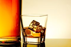 Glass of whiskey with ice cubes near bottle on table with reflection, warm tint atmosphere Stock Photo