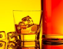 Glass of whiskey with ice cubes near bottle on table with reflection, warm tint atmosphere Stock Photography
