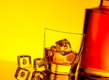 Glass of whiskey with ice cubes near bottle on table with reflection, warm yellow tint atmosphere Royalty Free Stock Photography
