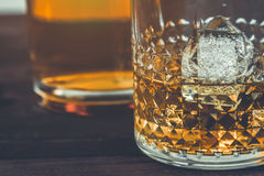 Glass of whiskey with ice cubes near bottle on wood table, warm atmosphere Stock Photos