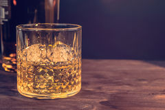Glass of whiskey with ice cubes near bottle on wood table, warm atmosphere Stock Photography