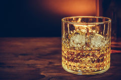 Glass of whiskey with ice cubes near bottle on wood table, warm atmosphere Royalty Free Stock Photos