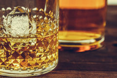 Glass of whiskey with ice cubes near bottle on wood table, warm atmosphere Royalty Free Stock Photo