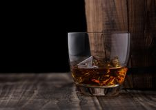 Glass of whiskey with ice cubes next to wooden barrel. Cognac brandy drink. Glass of whiskey with ice cubes next to wooden barrel. Cognac and brandy drink royalty free stock photography