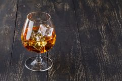 Glass of whiskey with ice cubes served on wooden planks. Vintage countertop with highlight and a glass of hard liquor Royalty Free Stock Image