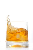 Glass of whiskey with ice cubes splashing Royalty Free Stock Photos