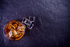 Glass of whiskey with ice cubes stock photos