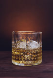 Glass of whiskey with ice cubes on wood table, warm atmosphere Stock Photo