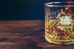 Glass of whiskey with ice cubes on wood table, warm atmosphere Royalty Free Stock Photo