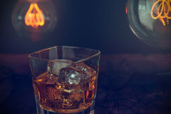 Glass of whiskey with ice cubes on wood table, warm atmosphere, time of relax with whisky with some  light warm bulb Royalty Free Stock Photo