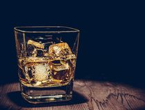 Glass of whiskey with ice cubes on wood table, warm atmosphere, time of relax with whisky Stock Photo
