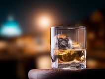 Glass of whiskey. With ice cubes on the wooden table with city view background