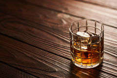 Glass of whiskey with ice cubes on wooden table Stock Photography