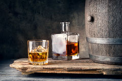 Glass of whiskey with ice decanter and barrel Stock Photo
