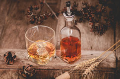 Glass of whiskey with ice decanter on wooden table Stock Photos
