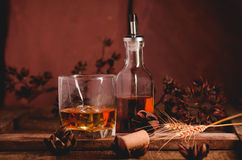 Glass of whiskey with ice decanter on wooden table Royalty Free Stock Photos
