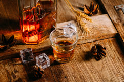 Glass of whiskey with ice decanter on wooden table Stock Image