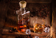 Glass of whiskey with ice decanter on wooden table Royalty Free Stock Images