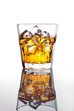 Glass of whiskey and ice on glass table Stock Images