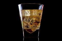 A glass of whiskey with ice isolated on a black background. Stock Image
