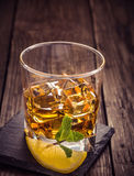 Glass of whiskey and ice with lemon and mint Royalty Free Stock Photos