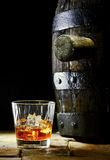A glass of whiskey with ice and an oak barrel Royalty Free Stock Photos