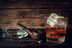 Glass of whiskey with ice and pipe on a wooden background. Royalty Free Stock Photography