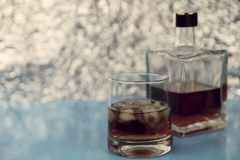 A glass of whiskey with ice and a square transparent bottle on a light blue background and silver bokeh. Free space on the left, horizontal, close-up, blur royalty free stock photos