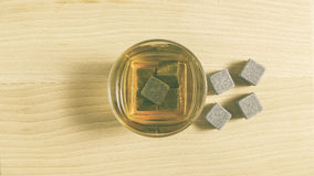 A glass with whiskey and ice stones on a wooden table. A glass with ice stones and cold whiskey on a wooden table, top view Stock Photo